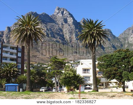 LANDSCAPE, TREES AND BUILDINGS IN THE FORE GROUND AND MOUNTAINS  IN THE BACK GROUND 12sd