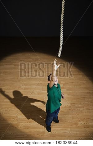 Mixed race boy reaching for rope