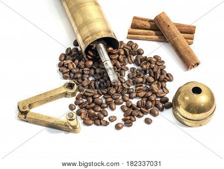 Manual grinder, old manual coffee mill and cinnamon on white