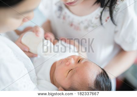 Sister and Mother takecare asian new born baby to feed and sleep in thr cradle