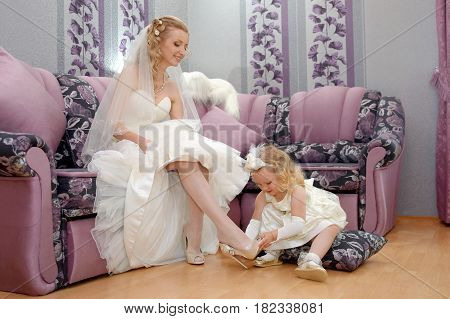 The little girl's mom is getting married. Daughter dresses mom bride wedding shoes
