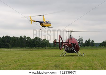 Two small helicopters take off from a green lawn