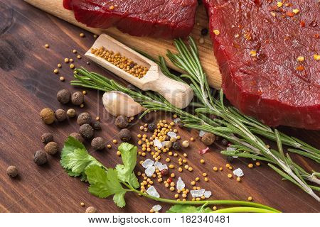 raw beef steak with ingredients for cooking on wooden Boards
