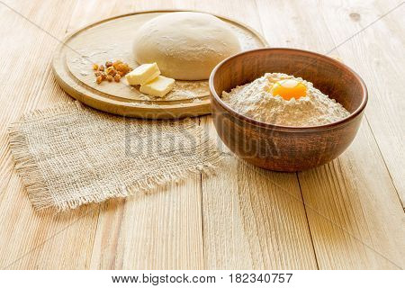 Ingredients for cooking dough sweet baking. Bowl of flour butter and eggs on a cutting board