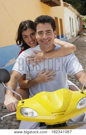 Couple riding scooter