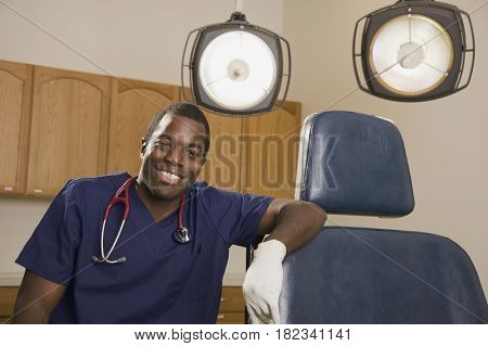 African dentist next to dentist's chair