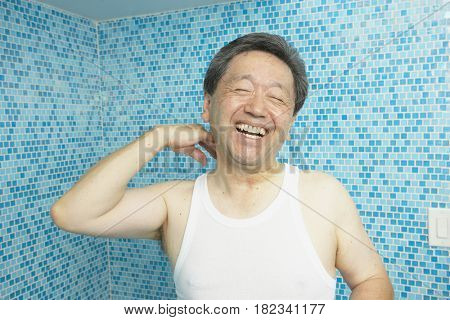 Laughing Asian man in bathroom
