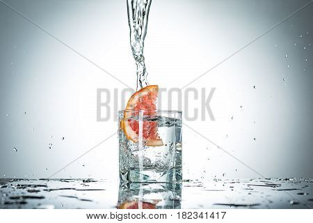 The water splash in glass with grapefruit of gray studio color