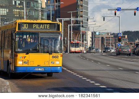 VILNIUS MARCH 16: Vilnius bus rides along a busy street on March 16 2017 in Vilnius Lithuania. Vilnius is the capital of Lithuania and its largest city.