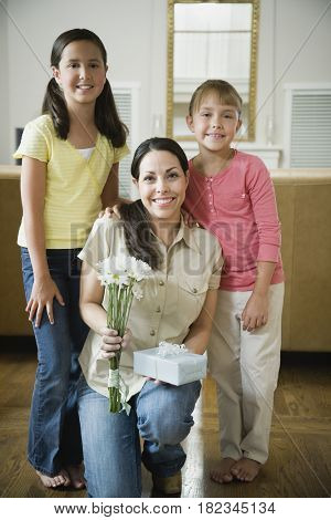 Hispanic mother and daughters with flowers and gift