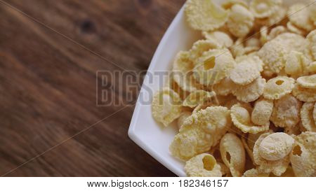 Corn flakes in white bowl with copyspace to the left. Concept of breakfast.