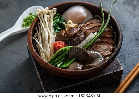 Ramen soup with duck and mushrooms over dark concrete background, close view.