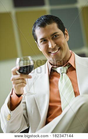 Hispanic businessman drinking red wine
