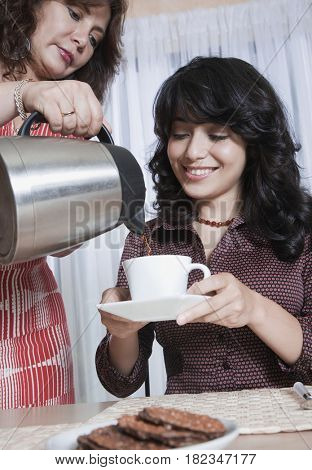 Mother serving daughter coffee and cookies
