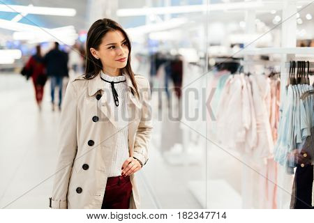Beautiful young woman shopping trendy clothes in shop
