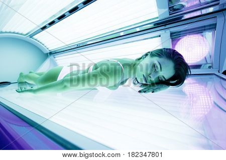 Beautiful sexy young brunette sunbathing in solarium