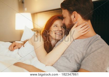 Sensual young couple in love in bed cuddling poster