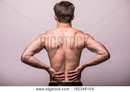 Close Up Of Man Rubbing His Painful Back On Grey Background.
