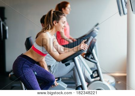 People traning in gym on various machines as part of cardio workout