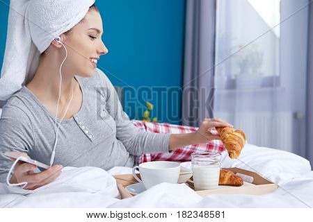 Portrait of a happy smiling latino hispanic woman eating a healthy breakfast in bed.