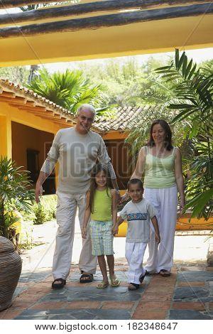 Hispanic grandparents standing with grandchildren