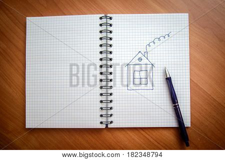 Drawn with a ballpoint pen the house with the pipe in the open notebook with the pages in the box