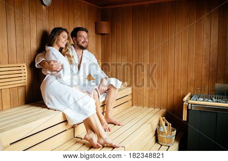 Healthy beautiful couple relaxing in sauna during wellness weekend poster