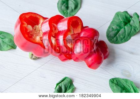 closeup of chopped sweet pepper on white background with spinach leaves