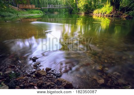 River deep in mountain forest. Brocken bridge at background. Long exposure