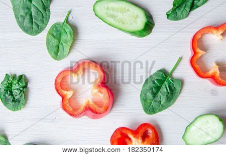 backgroud of chopped sweet pepper on white background with spinach leaves and cucumber