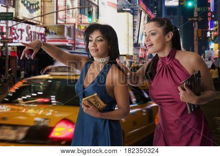 Hispanic women hailing taxi cab