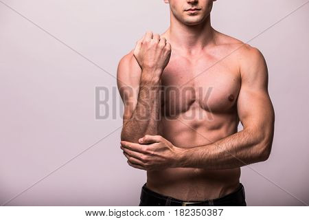 Young Man Having Pain In His Elbow On Grey Background
