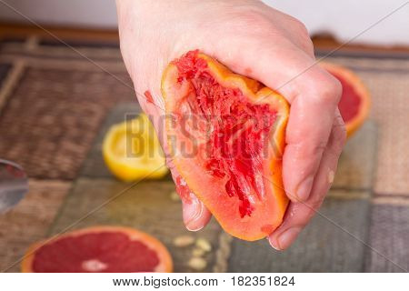 Hand squeezing grapefruit closeup. Photo can be used as a whole background.