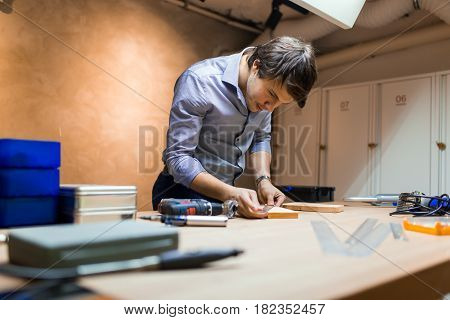 Handyman working with wood with precision tools at hand