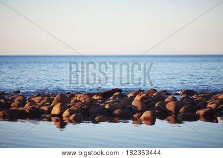 A ridge of boulders in the sea. Sunset time. Kangaroo Island, South Australia.
