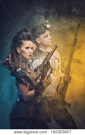 Cosplay Steampunk. Woman and Man with weapon of the Victorian era in an alternate history. Steam punk style with guns in colorful smoke.