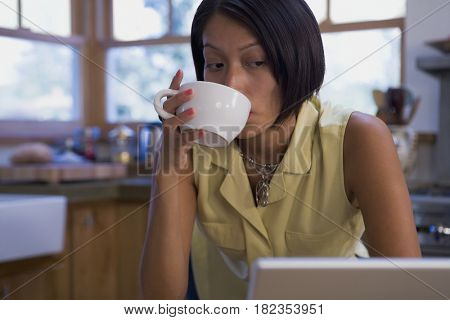 Native American woman drinking coffee and looking at laptop