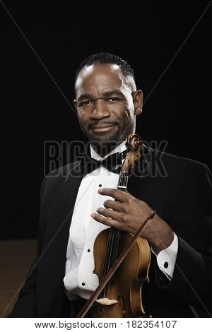 African American man in tuxedo posing with violin