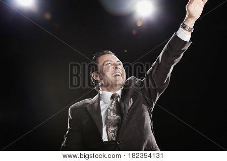Hispanic man waving under spotlights