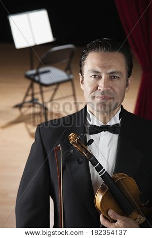 Hispanic man in tuxedo posing with violin