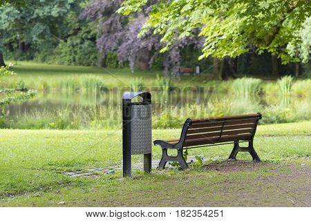 bench with dust bin next to it in a park