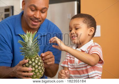 Antiguan father showing pineapple to son