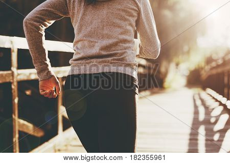 Female jogger running in beautiful sunset with a nice flare showing on photo