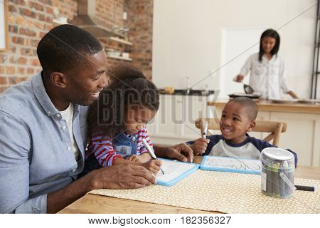 Father And Children Drawing At Table As Mother Prepares Meal