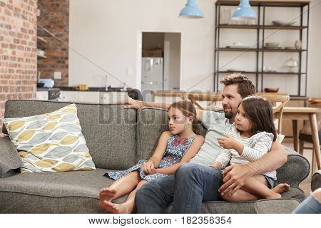 Father And Children Sit On Sofa In Lounge Watching TV