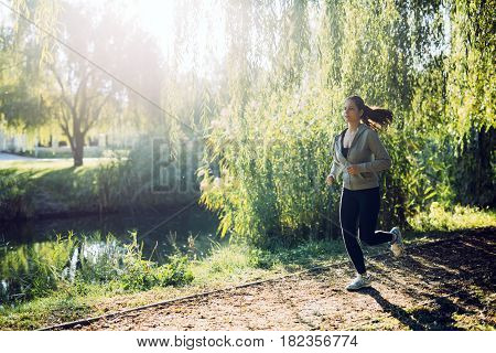 Fit female jogger running in nature surrounded by beautiful hanging trees