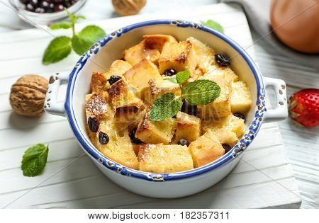 Delicious bread pudding with currant and mint in bowl on wooden board