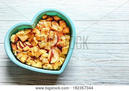Delicious bread pudding with apples in heart shape bowl on table