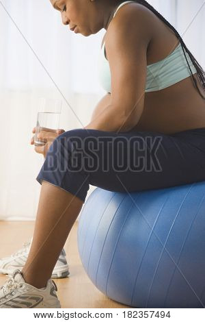 Pregnant African woman sitting on exercise ball drinking water