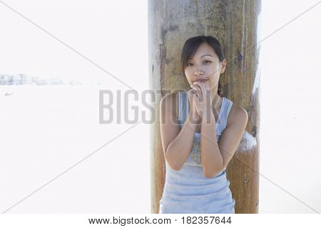 Asian woman standing in front of pillar at beach